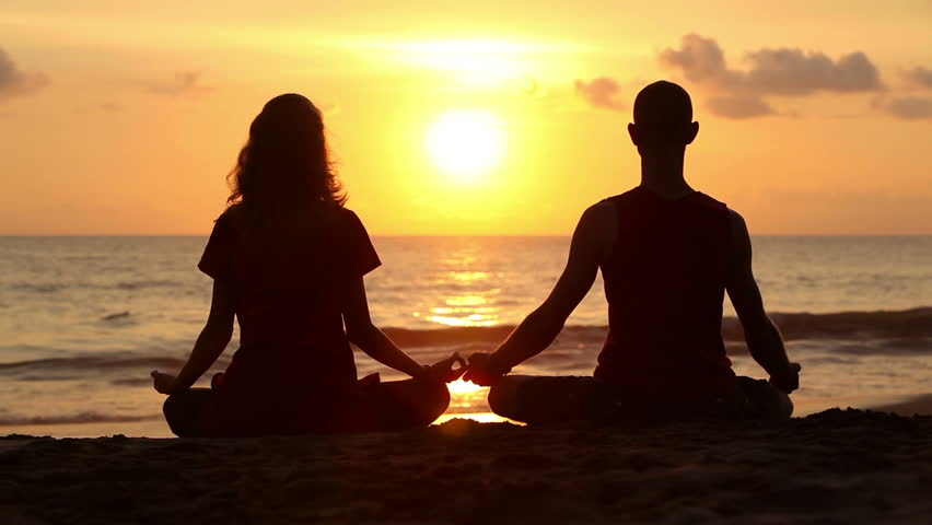 Couple sitting yoga on beach while sunset - HD stock footage clip