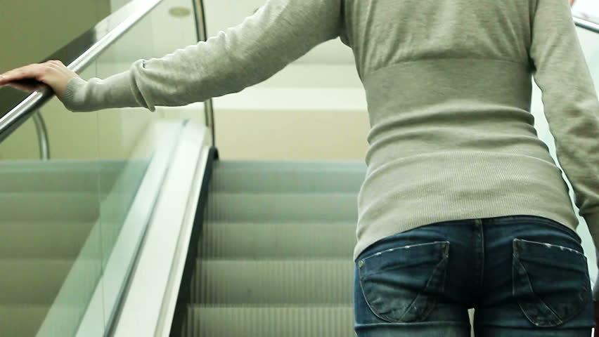 Young woman moving on escalator