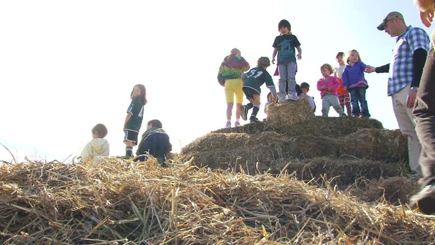 PORTLAND, OREGON - CIRCA 2012: Kids playing on haystacks jump off and laugh on