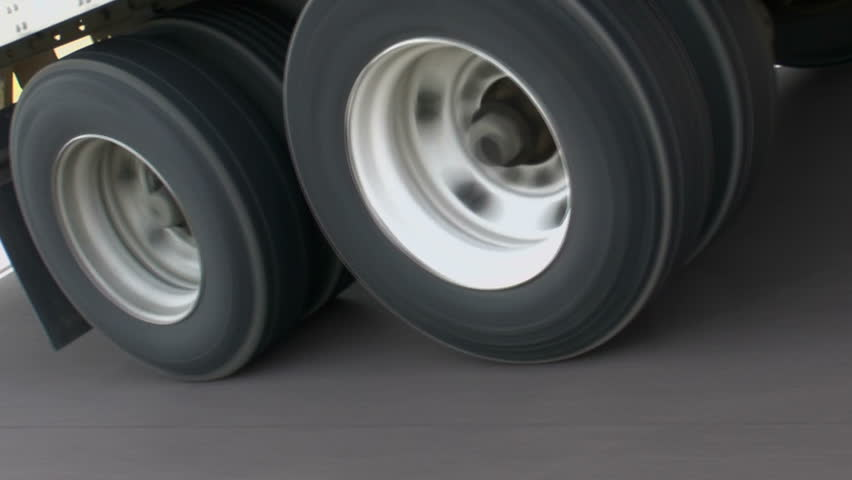 Side, frontal view, close up, of eighteen-wheeler truck tires in motion, driving along smooth, open highway. 108op