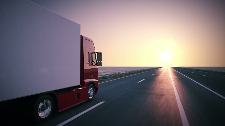 Truck on the road with sunset in the background. Large delivery truck is moving towards setting sun.
