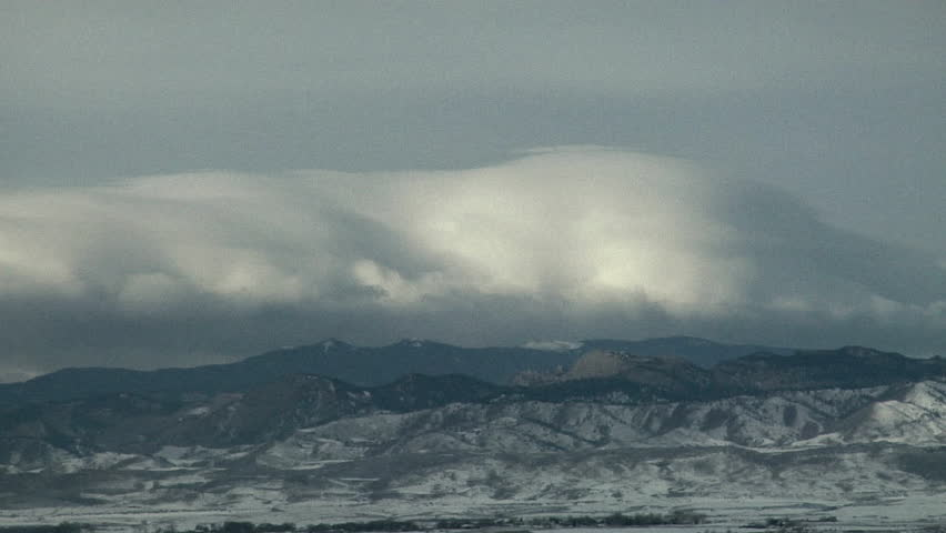 Downslope Winds. Winter cap cloud dissolves as it is swept down the lee slopes of the mountains - HD stock video clip