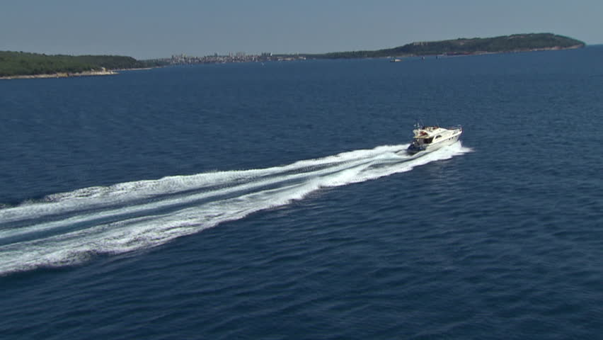 A speedboat speeds across Adriatic sea near islands. Aerial helicopter shot.