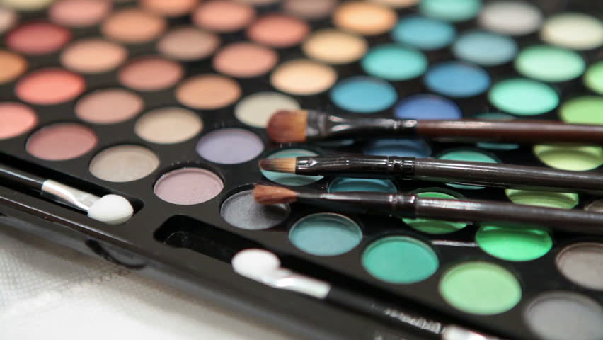 Make-up brushes laying on colorful cosmetic palette. Camera rotation | Shutterstock HD Video #3663578