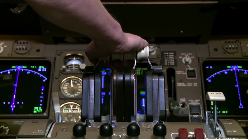 Detail of 747 pilot's hand as he pulls back on jet throttles while plane is on