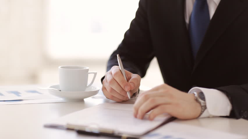 man in suit and tie signing a contract