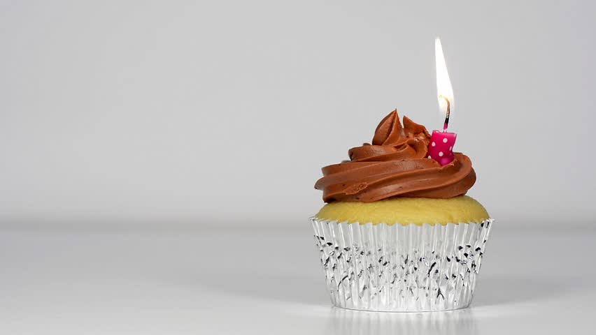 Delicious Vanilla Cupcake with Chocolate Frosting and Burning Birthday Candle #3678968