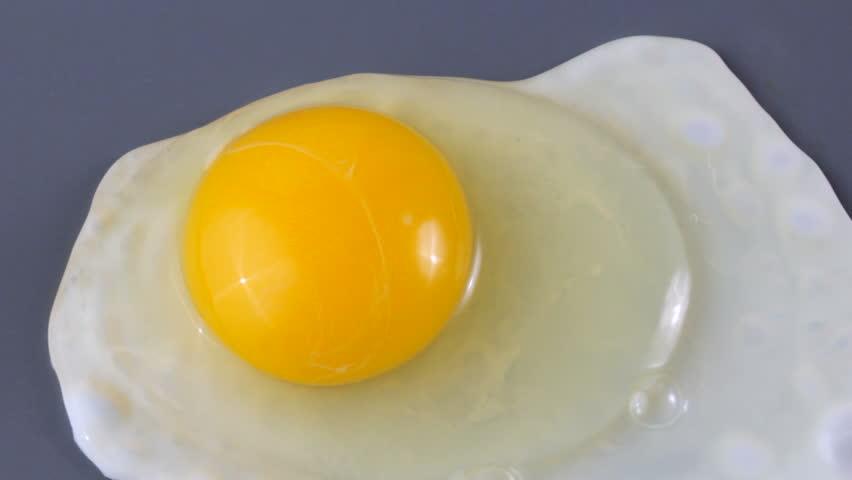 Close up of hands breaking egg over griddle, cooking sunny side up