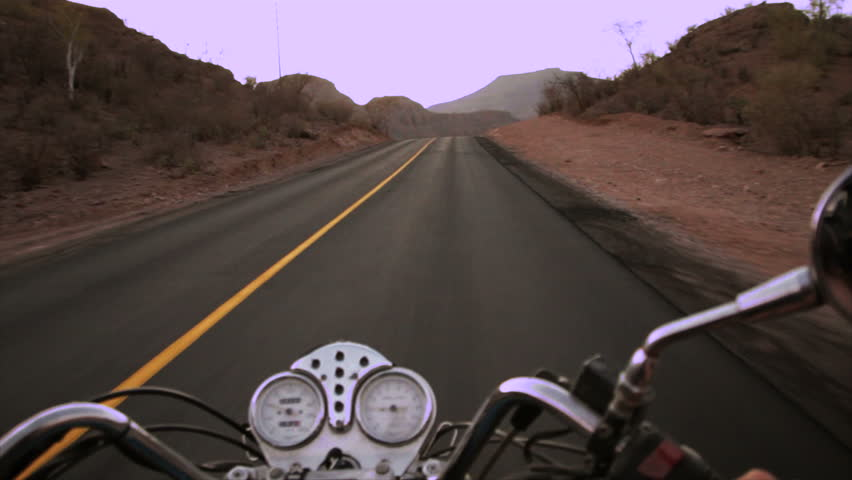 Foreground handlebars of a motorcycle that rides the desert road - HD stock video clip