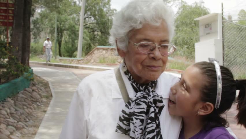 Grandmother hugging her little granddaughter at the park