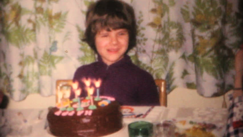 MOOSIC, PENNSYLVANIA, 1968: A cute little girl enjoys blowing out the candles at her birthday party in 1968.