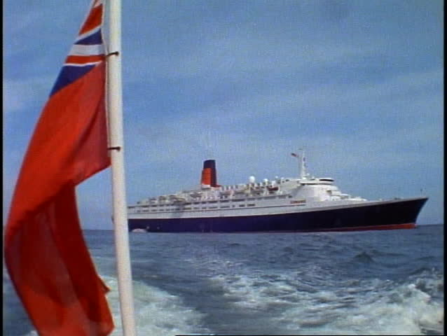 Queen Elizabeth 2, QE2 at anchor, on tender moving away, ensign waving, wide shot - SD stock footage clip