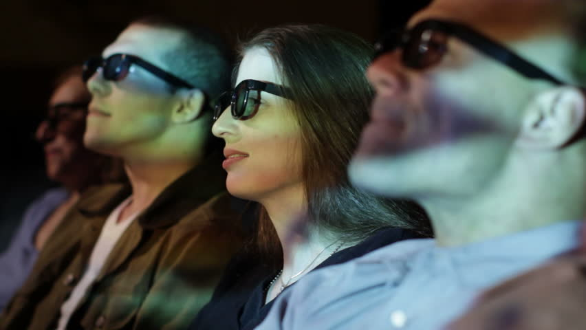Young woman and friends react to dramatic action as she watches a 3D movie.