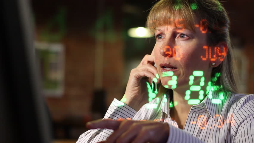 Woman on the phone with stock ticker symbols projected across her as she makes