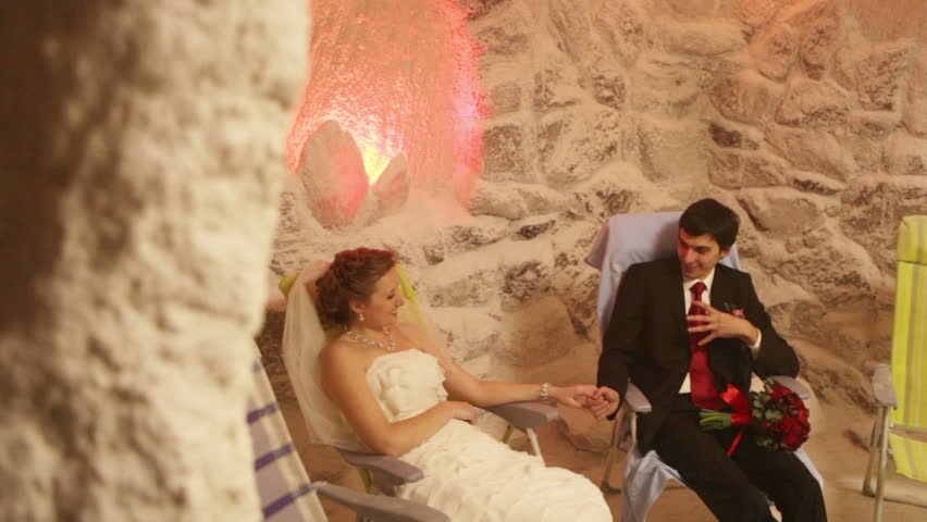 Young couple in a salt cave therapy sits and taste the salt - HD stock video clip