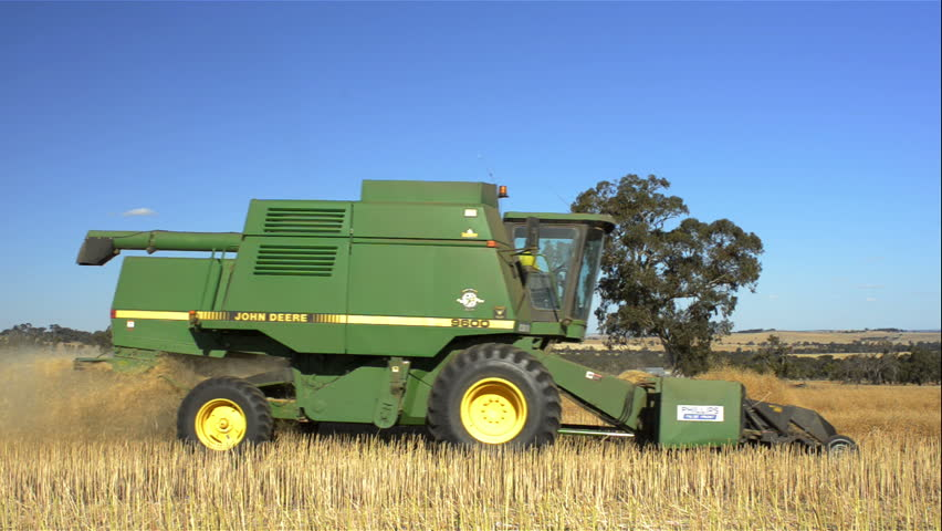 WAGIN, AUSTRALIA - November 20, 2012: An Australian farmer harvesting a canola crop, that has been swathed into windrows ready for harvest, driving by the camera.