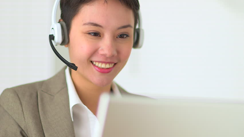Asian customer service representative with headset in call center - HD stock video clip