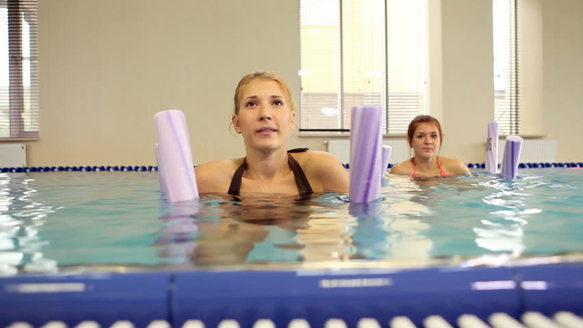 Group of smiling women with aqua tubes doing exercise in Fitzroy swimming pool group fitness