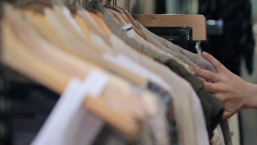 Woman's hands run across a rack of clothes, browsing in a boutique. Head-on view with rack focus.