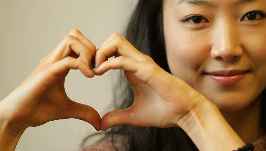 Beautiful young Asian woman making love heart gesture with hands | Shutterstock HD Video #3735740