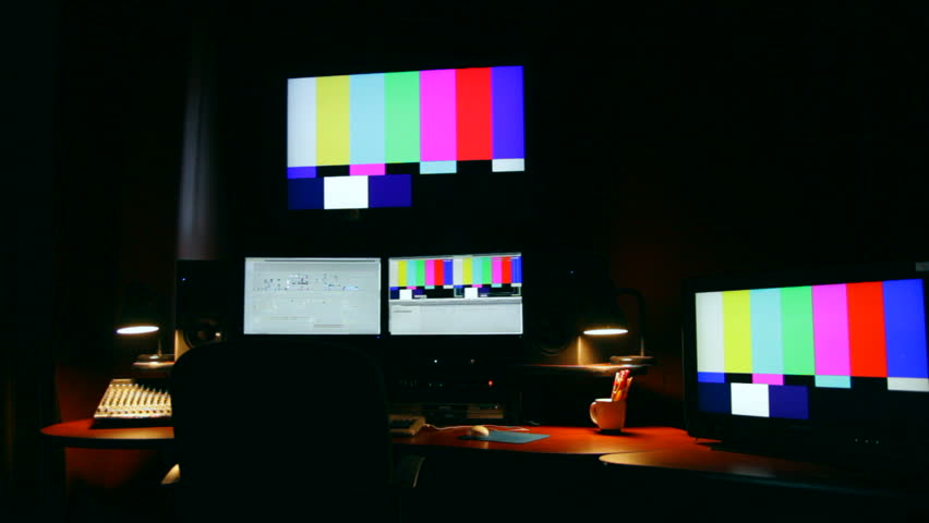 Slow dolly of a dark post production edit suite.