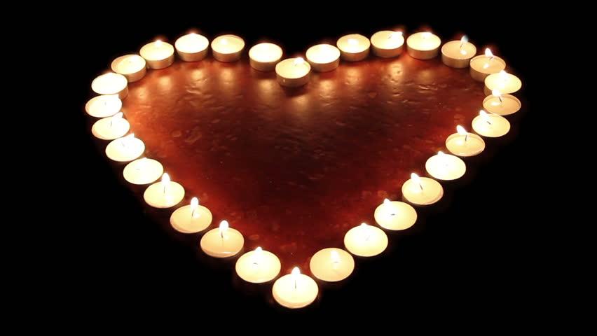 Fiery heart. Candles arranged in a heart shape light up, then go off
