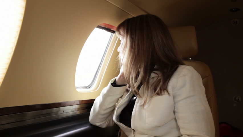 Smartly dressed attractive woman sitting in a private jet, enjoying the atmosphere. Mid shot from front angle.