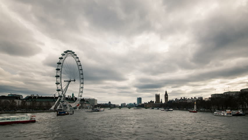 London skyline with London Eye and Westminster on Thames river in a cloudy day. - HD stock footage clip