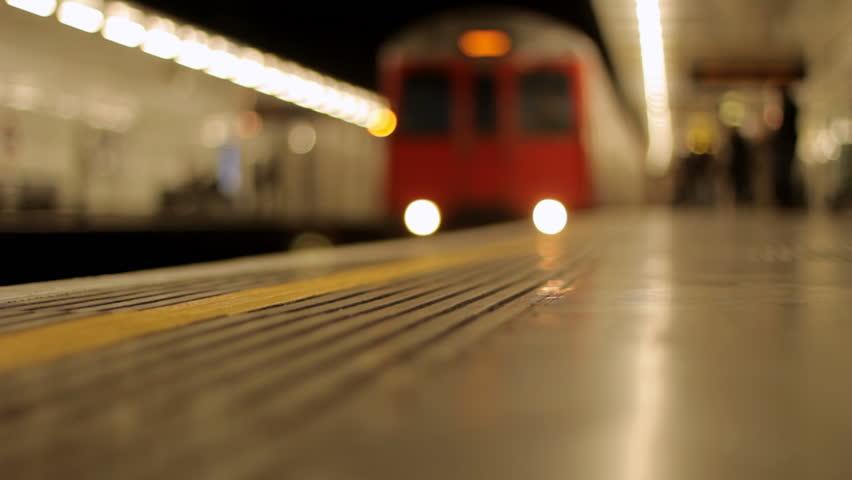 London Underground - London underground train stops at a platform and passengers embark and disembark.