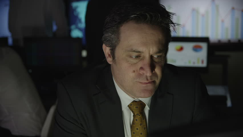 A mature businessman is working late at night in a dark office filled with computer screens. Other members of his team can be seen hard at work in the background. In slow motion. - HD stock footage clip