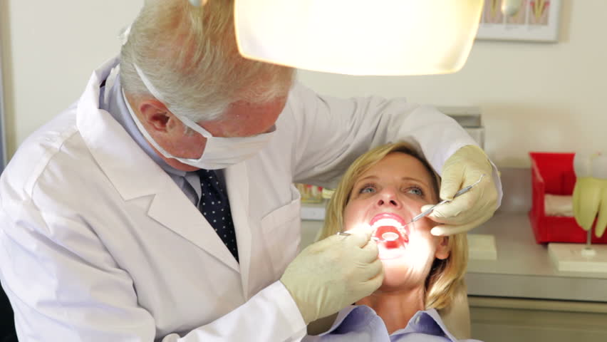 Dentist examining teeth of female patient. Shot on Canon 5d Mk2 with a frame rate of 30fps - HD stock video clip