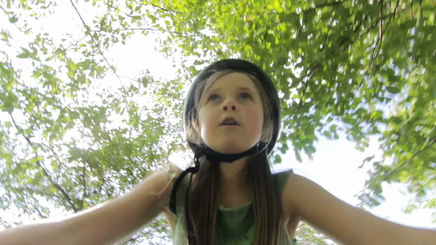 Child Cycling - A little girl with cycle helmet cycling under some trees in a park. (camera attached to handlebars) pov - HD stock footage clip