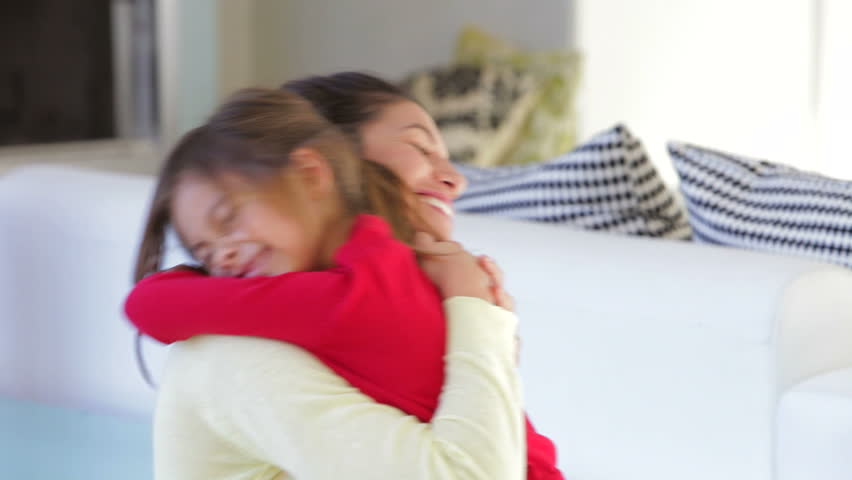 Daughter rushes into mother's arms at home and gives her a big hug. Shot on Canon 5d Mk2 with a frame rate of 30fps
