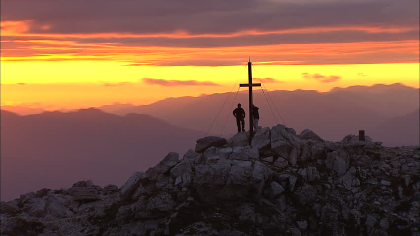 Sunset over the Mountains / Italy / Alp. People stand near cross silhouetted on mountain with flare.