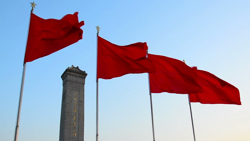 red flags flying in front of the monument in the centre of tiananmen square Beijing China