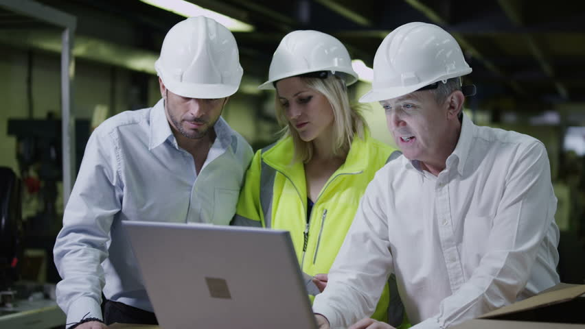 Male and female warehouse workers are looking at a laptop computer and discussing the logistics of their business. In slow motion.