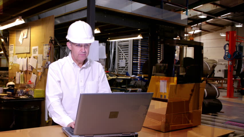Time-lapse of busy workers in a warehouse or factory. One worker stands in front of his laptop computer, while his colleagues rush around preparing goods for packaging and delivery.