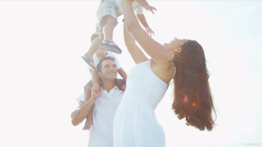 Attractive Hispanic couple enjoying quality time with little kids on beach sun lens flare shot on RED EPIC - HD stock footage clip