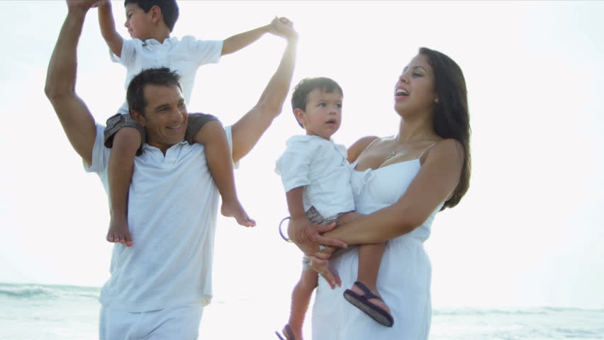 Happy Hispanic parents enjoying quality time with young children walking on beach sun lens flare shot on RED EPIC - HD stock footage clip