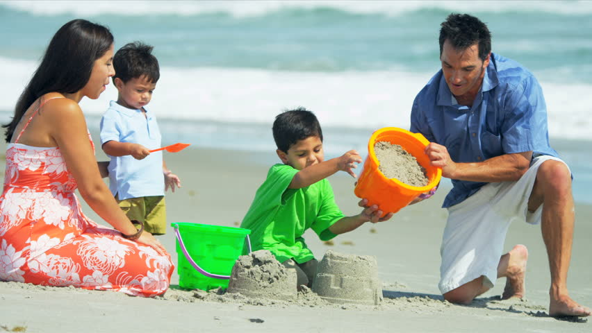 Happy Latin American boys building sand castles with young parents on summer beach shot on RED EPIC - HD stock video clip