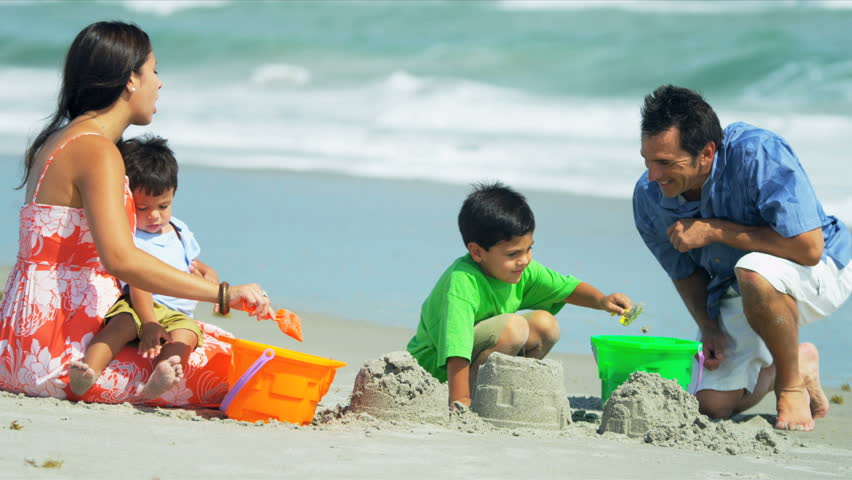 Little Hispanic brothers playing together with young father and mother on beach shot on RED EPIC - HD stock footage clip