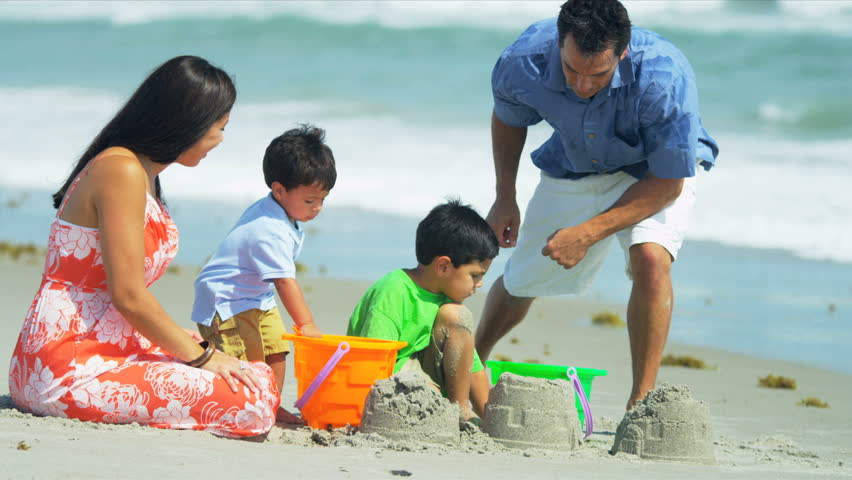 Happy Hispanic family building sand castles on beach shot on RED EPIC - HD stock video clip