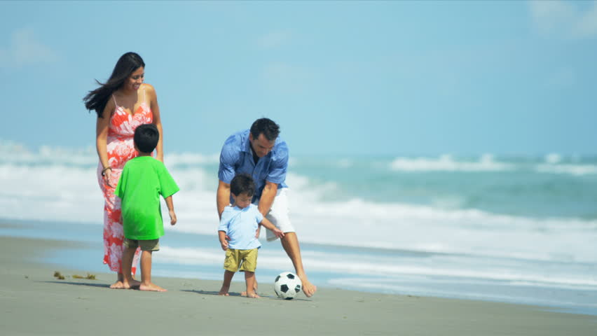 Hispanic young loving family spending vacation on beach playing soccer shot on RED EPIC - HD stock footage clip