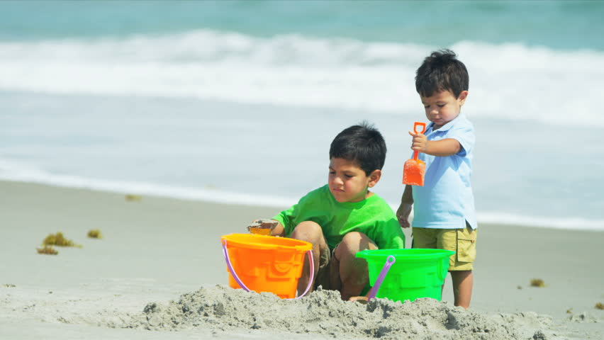 Little Hispanic brothers playing together with young father on beach shot on RED EPIC - HD stock footage clip
