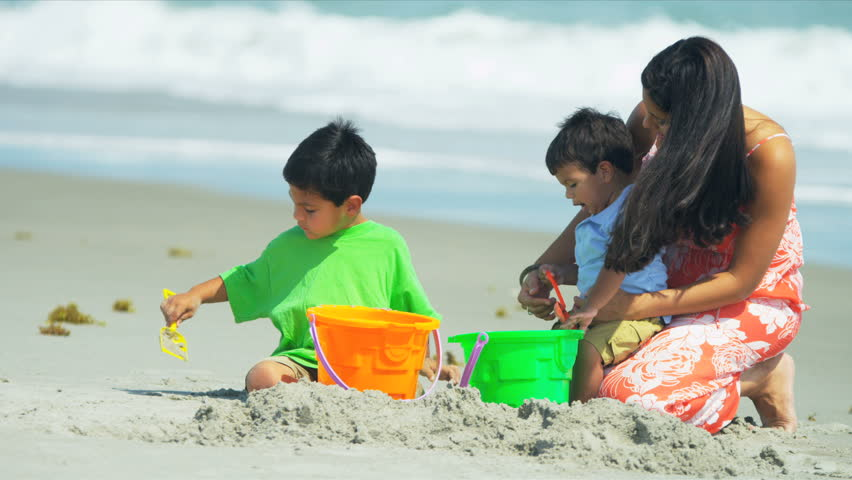 Happy Hispanic mother helping kids with sand castles on beach shot on RED EPIC - HD stock video clip