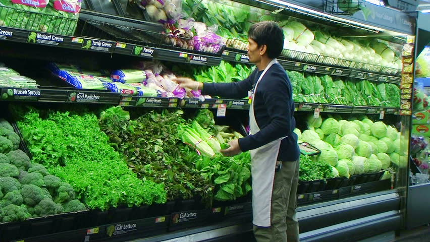 Worker facing  fresh vegetables in grocery store.  - HD stock footage clip