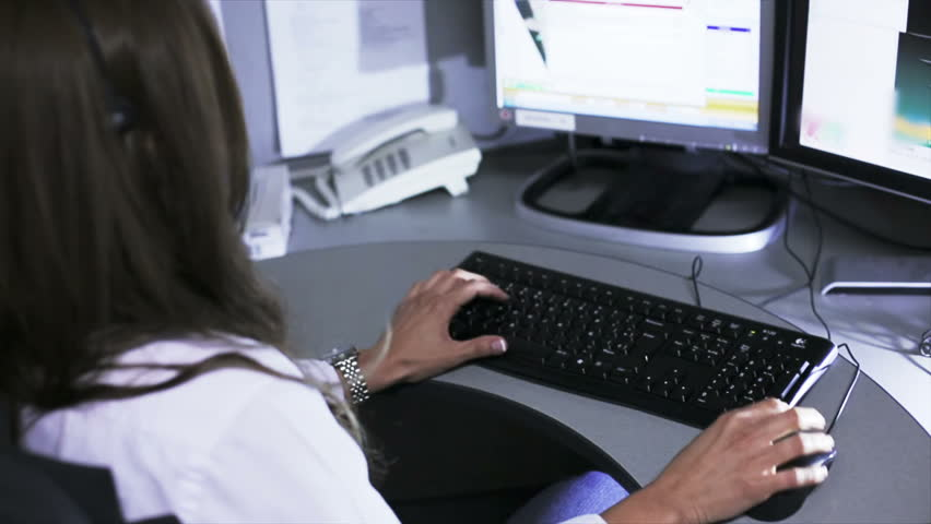 woman typing information of a call on the 911 emergency center