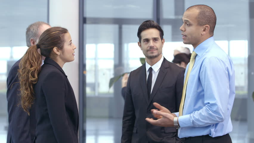 Confident and attractive business team of mixed ages and ethnicity meet and shake hands in the lobby of a busy modern office building.