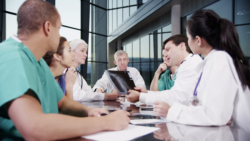 A diverse team of medical personnel are having a meeting in a light, modern private health care facility. They are discussing the x-ray of a patient's chest and looking for a diagnosis. | Shutterstock HD Video #3848780