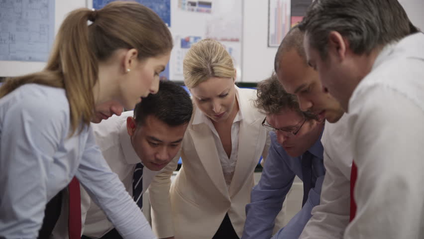 Diverse team of professionals, brainstorming in a business meeting. They are looking over a series of sales figures and diagrams and discussing their business development.  - HD stock footage clip